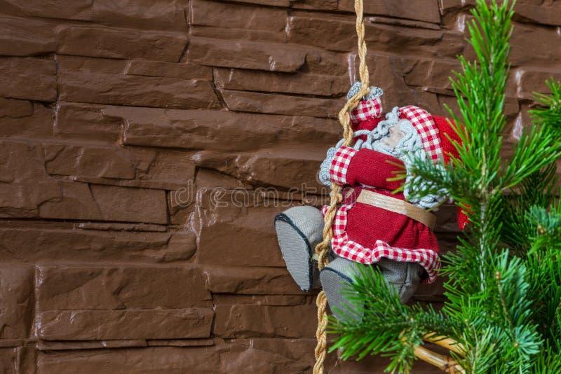 Julsammansättning av en julgran och en Santa Claus som klättrar ett rep fotografering för bildbyråer