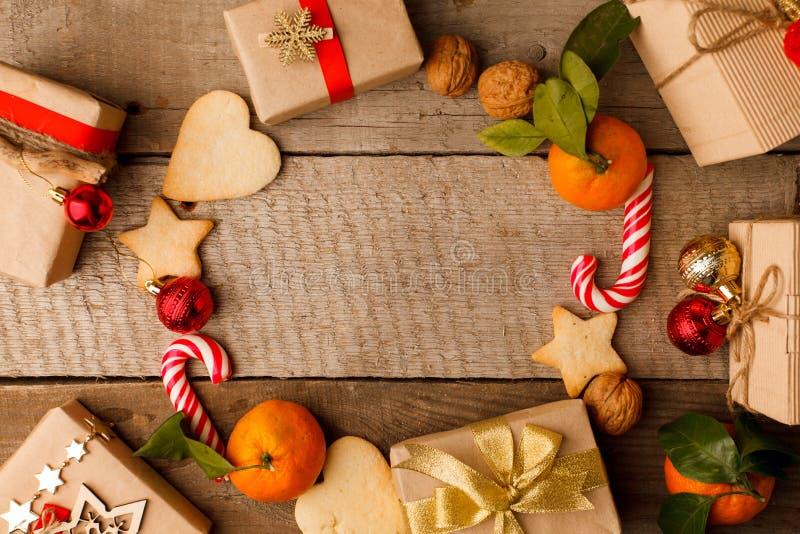 Julsammansättning av olika gåvaaskar i hantverkpapper dekorerade röda guld- band och semestrar sötmapepparkakakakor royaltyfri fotografi