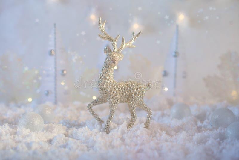 Julsammansättning gjorde av julbollar och statyetten av renen på blå vinterbakgrund Minsta utformat feriekort royaltyfri bild