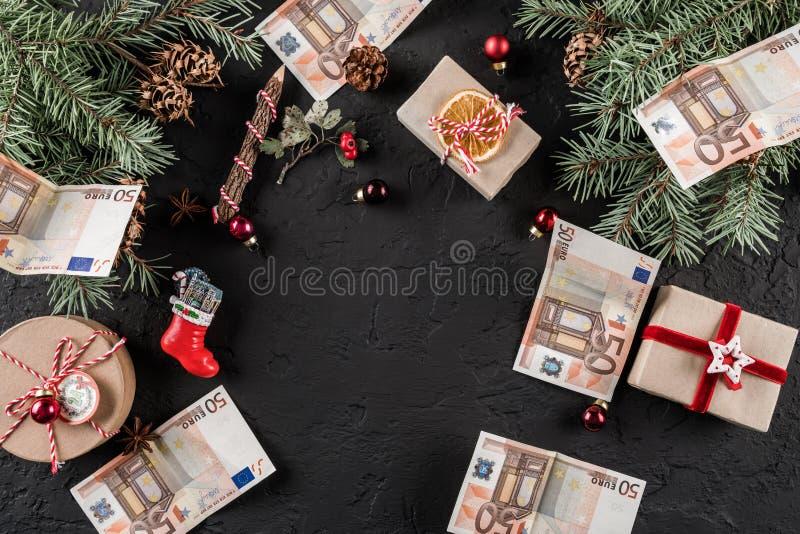 Julsammansättning med gåvaaskar, granfilialer, sörjer kottar och pengareuro på mörk feriebakgrund royaltyfri fotografi