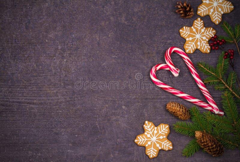 Julsammansättning med godisrottingar, granträdfilialer och ljust rödbrun brödkakor royaltyfri fotografi