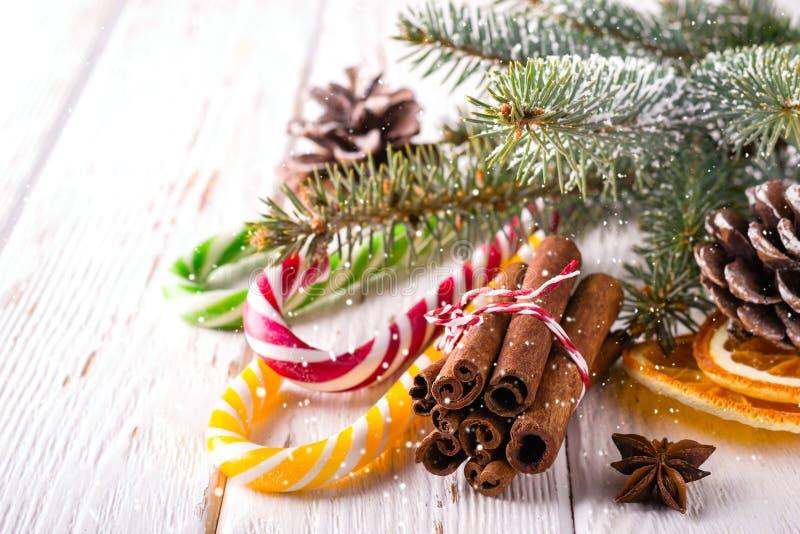 Julsammansättning med godisrottingar och kanelbruna pinnar på vit träbakgrund royaltyfria bilder