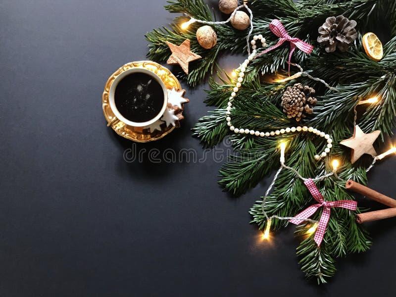 Julsammansättning med granträdfilialer och julpynt, en kopp kaffe med kanelbruna kakor royaltyfria foton