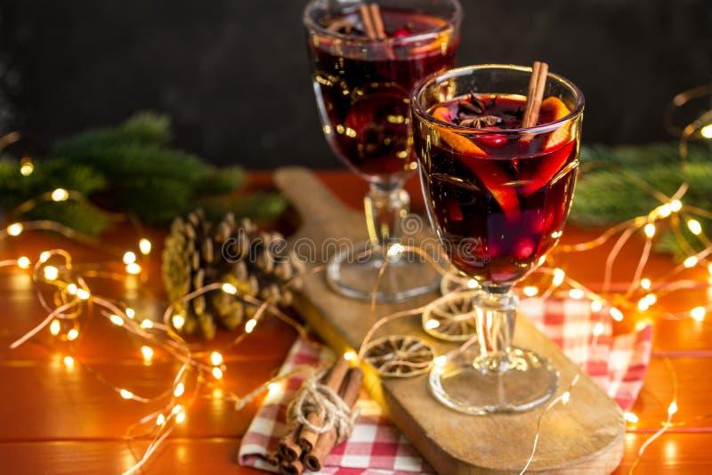 Julsammansättning med kryddigt funderat vin, ledde ljus och sörjer kottar på mörk bakgrund fotografering för bildbyråer