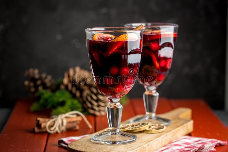 Julsammansättning med kryddigt funderat vin och att sörja kottar på röd bakgrund royaltyfri foto