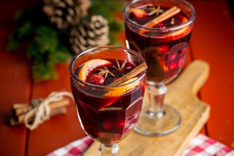 Julsammansättning med kryddigt funderat vin och att sörja kottar på röd bakgrund royaltyfria bilder