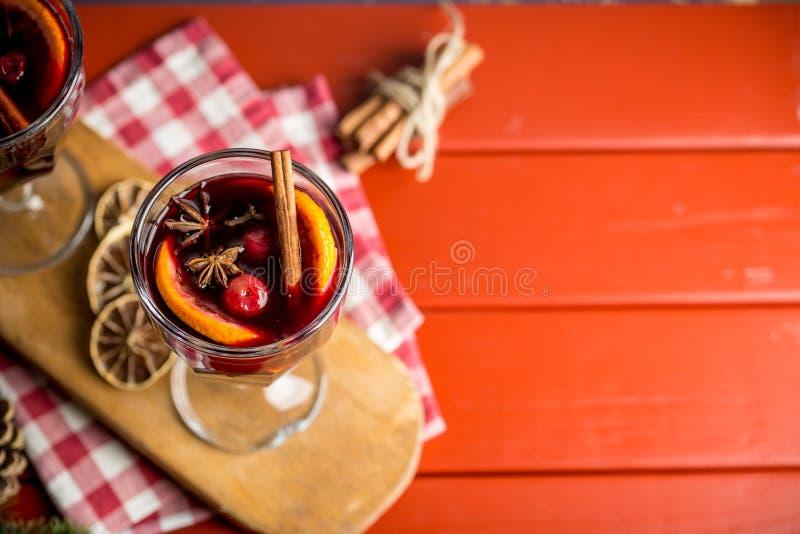 Julsammansättning med kryddigt funderat vin och att sörja kottar på röd bakgrund arkivfoton