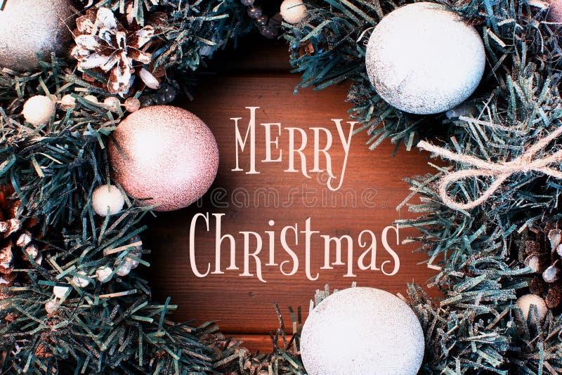 Julsammansättning, ram Den glade julen för inskrift Filialer av en julgran, grankottar och bollar royaltyfri fotografi