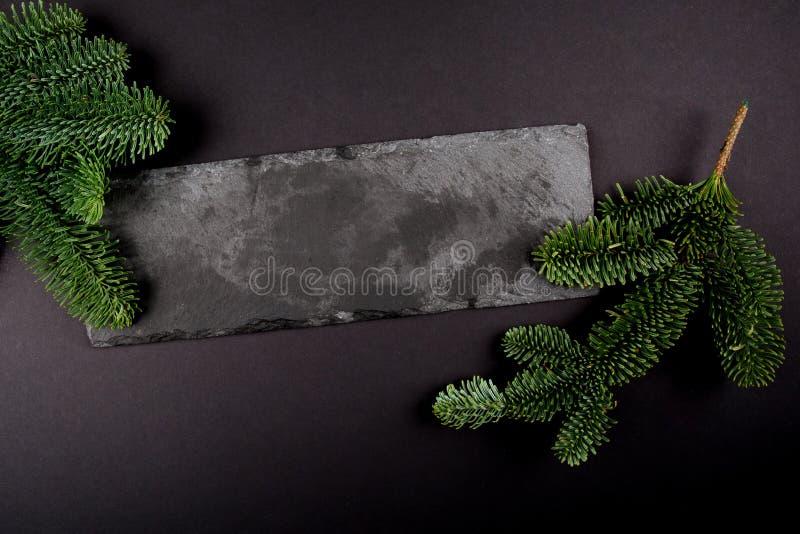 Julsammansättningsmall, dekorativt kopieringsutrymme Mörkt juljärnekträd - gräsplan på stenen Top beskådar Vintersmattrande arkivfoton