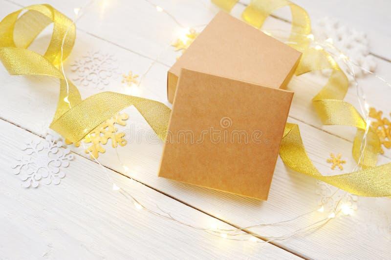 Julsammansättningsmodell Boxas på en bakgrund av snöflingor, en julgran, ett guld- band royaltyfri bild