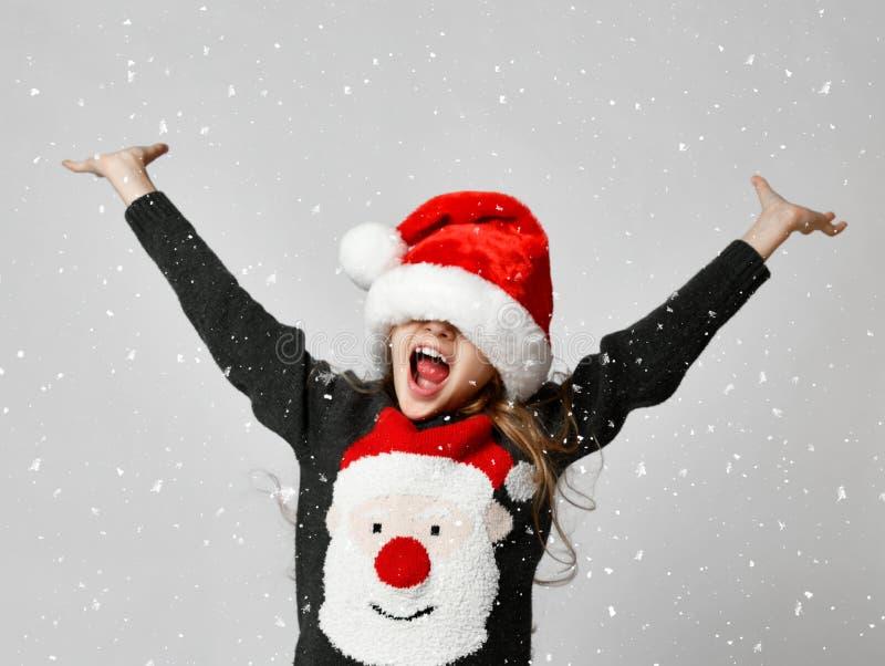 JulSanta Claus hjälpreda i röd hatt som ler liten flickaungen med händer upp spridning arkivbilder