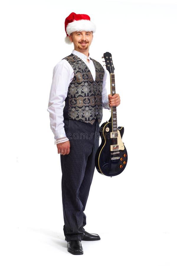 Julsanta man med den elektriska gitarren royaltyfria foton