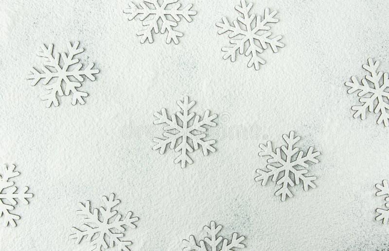 Julsnö flagar konturmodellen på Snowy White bakgrund som pudras med mjöl För feriehälsning för nytt år kort Baka royaltyfri foto