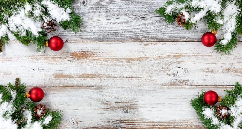 Julsnö täckte vintergröna filialer och röd bolldecoratio arkivbild