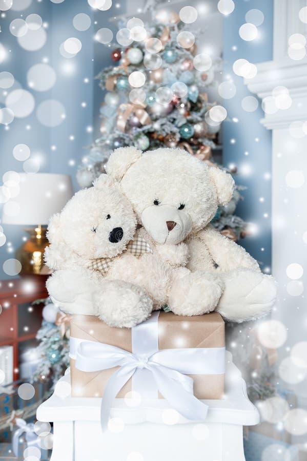 Julstämning, två vita leksaksbjörnar mot bakgrund av en vit dekorerad julgran Väntar på ett mirakel, New royaltyfri bild