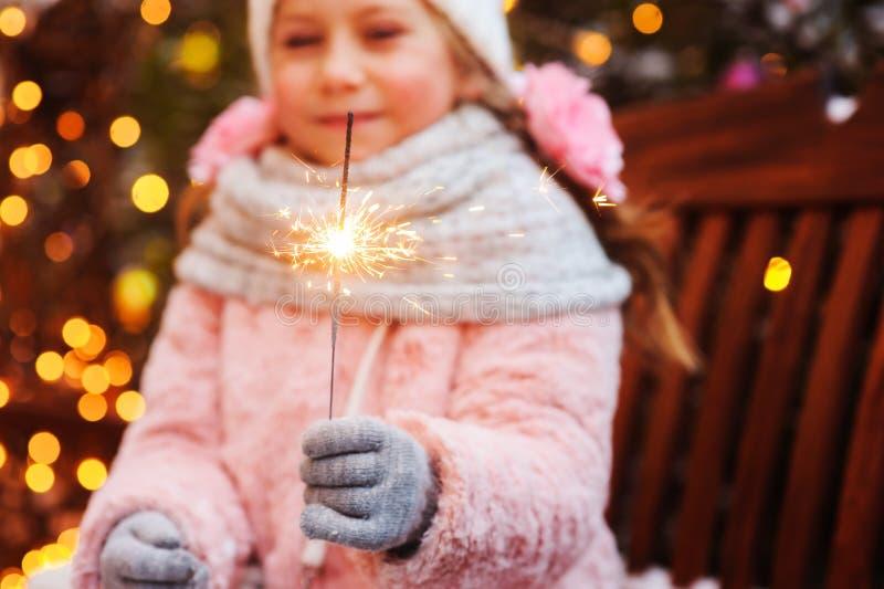 julstående av det hållande brinnande tomteblosset för lycklig barnflicka eller utomhus- fyrverkeri, royaltyfri foto