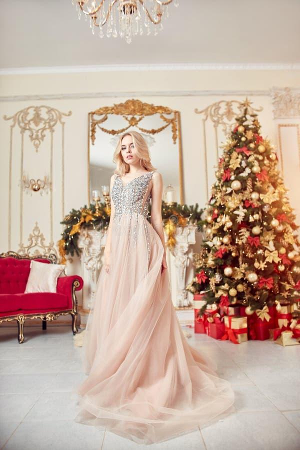 Julstående av en flicka i en blänka festlig klänning på bakgrunden av juldekoren i elegant inre royaltyfri foto