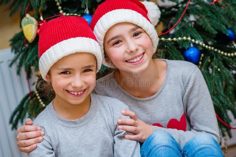 Julstående av två små flickor arkivfoto