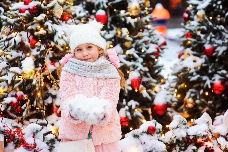 julståenden av den lyckliga barnflickan som går utomhus- snöig vinter, dekorerade träd på bakgrund arkivfoto