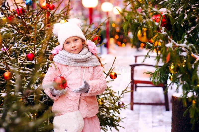 julståenden av den lyckliga barnflickan som går utomhus- snöig vinter, dekorerade träd på bakgrund fotografering för bildbyråer