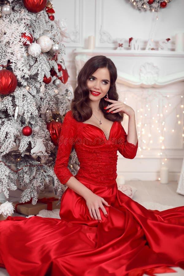 Julståenden av den lyckliga le flickan i den röda klänningen som sitter vid det snöig xmas-trädet, brunett med röda kanter, manic arkivbild