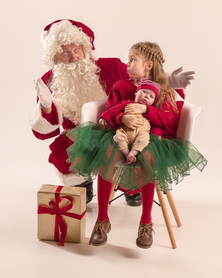 Julståenden av gulligt litet nyfött behandla som ett barn flickan, iklädd julkläder, studioskottet, vintertid arkivbild