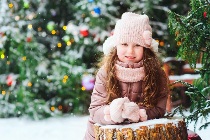 Julståenden av lyckligt spela för ungeflicka som är utomhus- i snöig vinterdag, granträd som dekoreras för nytt år, semestrar fotografering för bildbyråer