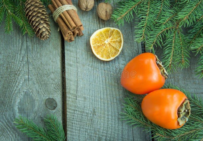 Julstilleben med den nya persimonet och kanel med sörjer trädet på träbakgrund Top beskådar royaltyfri fotografi