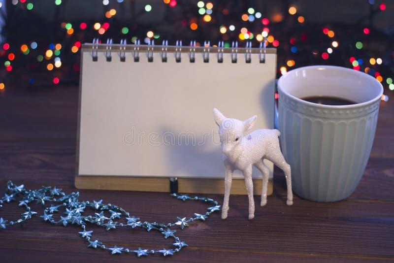Julstilleben med kaffe, leksaken och en anteckningsbok royaltyfria foton