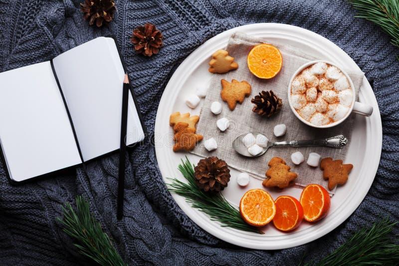 Julstilleben med varm kakao, tangerin, kakor och den tomma anteckningsboken på stucken bakgrund från över Lekmanna- lägenhet arkivfoto