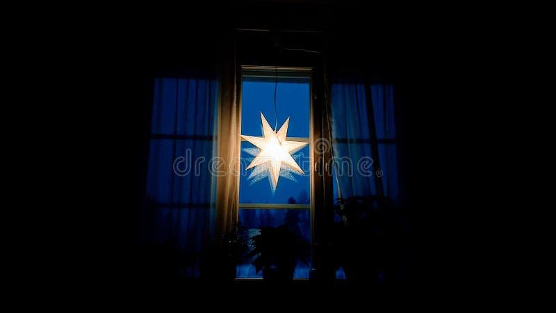 Julstjärna på fönstret på natten royaltyfria bilder