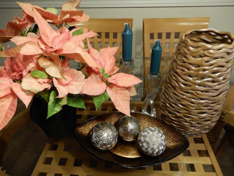Julstjärnablommor, vaser och stearinljus i en höjdpunktskärm arkivbilder