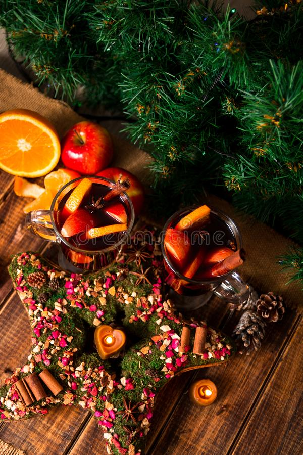 Julstjärnan nära funderade vin med frukter och kryddor på trätabellen Xmas-garneringar i bakgrund exponeringsglas två Vinterwarmi royaltyfria bilder