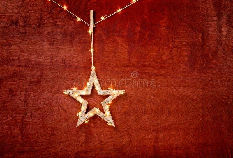 Julstjärnaprydnad som slås in i ljus på rött royaltyfri bild