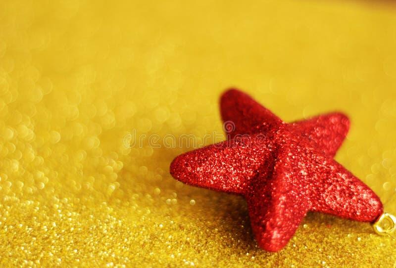 Julstjärnaprydnaden, rött och guld- blänker royaltyfri fotografi