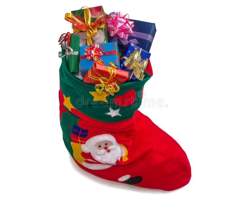 Julstrumpa med gåvor på vit royaltyfri foto