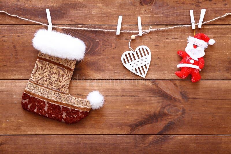 Julstrumpa, santa och hjärta som hänger på brun träbakgrund, dekorativa xmas-leksaker på den wood tabellen, köpande gåvashoppi royaltyfri fotografi