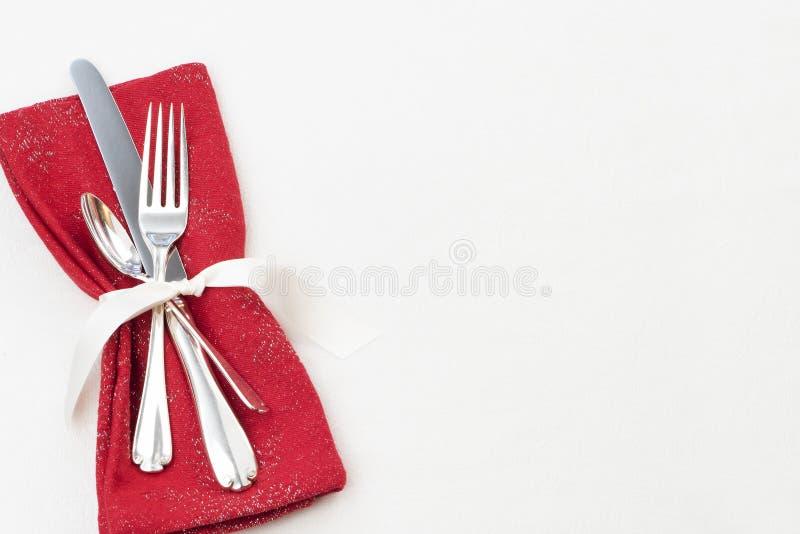 Jultabellen förlägger inställningen med bestick, den röda torkdukeservetten på vit borddukbakgrund med tomt rum eller utrymme för royaltyfri fotografi