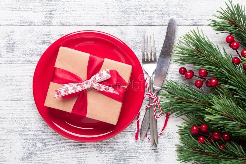 Jultabellinställning med den röda plattan, gåvaasken och bestick på ljus träbakgrund Granträdfilial, järnekbär Top beskådar fotografering för bildbyråer