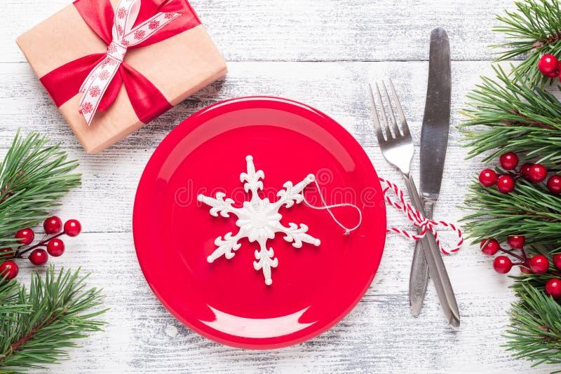 Jultabellinställning med den röda plattan och bestick på ljus träbakgrund Granträdfilial, järnekbär Bästa sikt med kopian royaltyfri bild