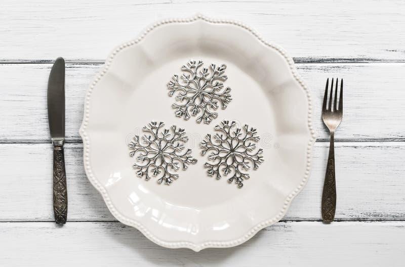 Jultabellinställningen, försilvrar snöflingor på en vit platta, tappningbestick, gaffel och kniv Vit träträtabell Top beskådar arkivbild