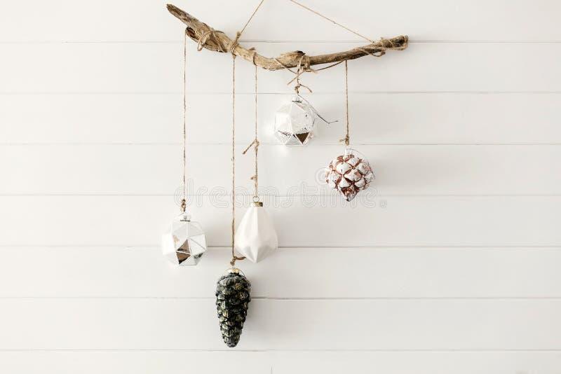 Jultappningleksaker som hänger på träbohofilial på bakgrund av den vita väggen i festligt modernt rum Stilfulla exponeringsglaspr royaltyfri bild