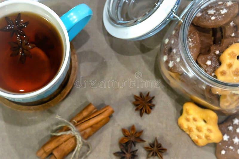 Julte med kryddor, kopp te med apelsinen, kanel, anis, kakor i en form av stjärnan på träbakgrund royaltyfria bilder