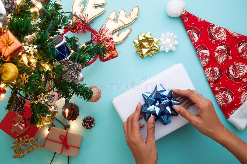 Jultema med kvinnan som slår in gåvaasken Lekmanna- lägenhet, bästa sikt arkivbild