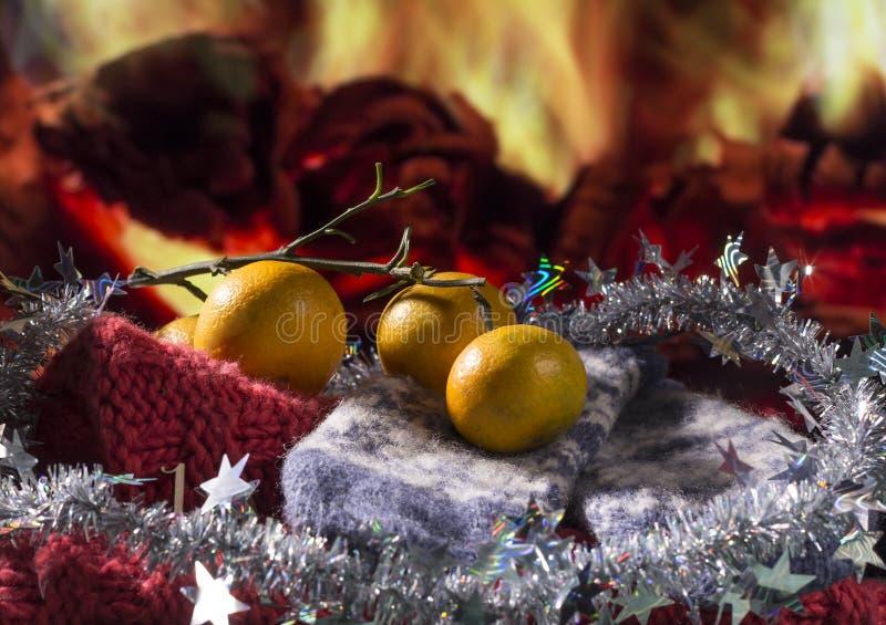 Jultema med tangerin, handskar och garneringar på spisbakgrund arkivfoto