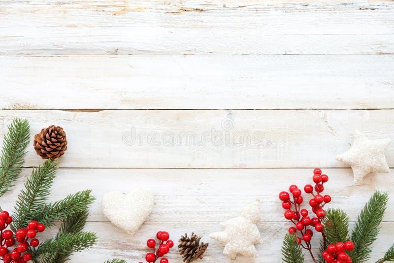 Jultemabakgrund med att dekorera beståndsdelar och prydnaden som är lantliga på den vita wood tabellen royaltyfria bilder