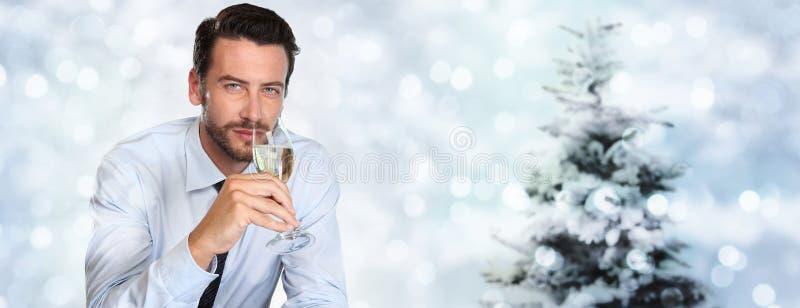 Jultemat, man dricker ett exponeringsglas av mousserande vin på suddigt arkivfoton