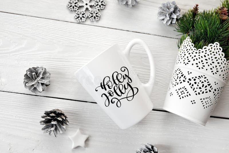 Jultext Holly Jolly på en vit rånar med en juldekor Lekmanna- lägenhet, fotomodell för bästa sikt royaltyfri fotografi