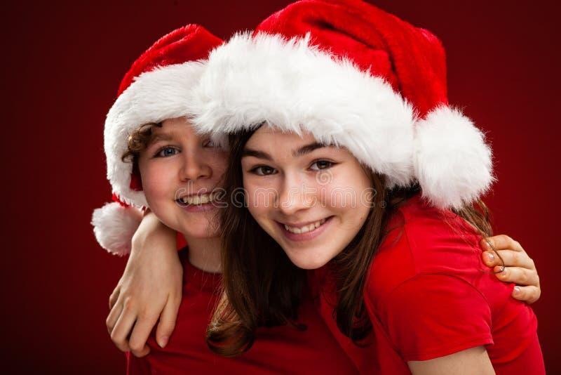 Jultid - flicka och pojke med Santa Claus Hats arkivfoton