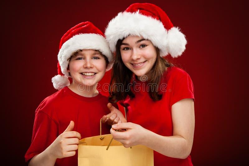 Jultid - flicka och pojke med Santa Claus Hats royaltyfria foton